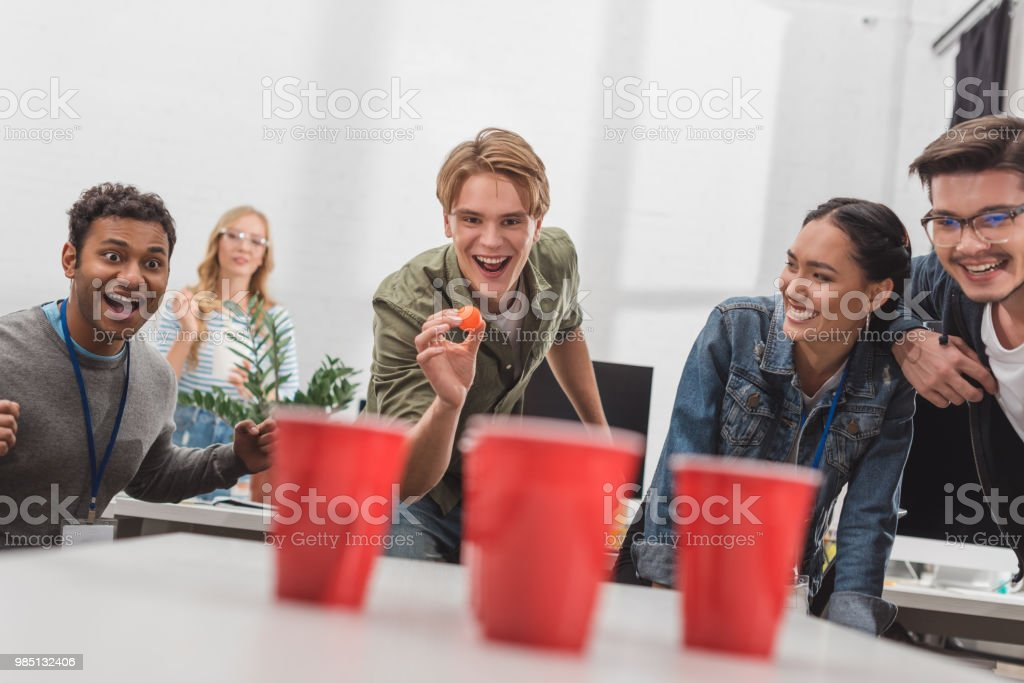 young attractive people playing beer pong at modern office after work stock photo