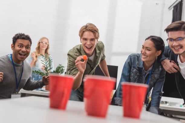 aantrekkelijke jongeren bier pong spelen op moderne kantoor na het werk - beirut stockfoto's en -beelden