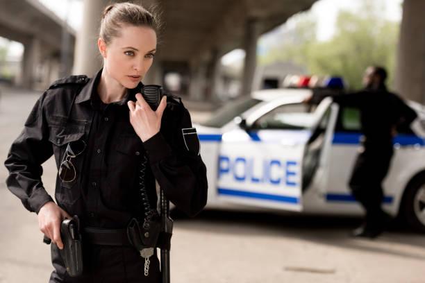 joven atractivo policía con walkie-talkie socio borrosa cerca de coche en el fondo - oficial rango militar fotografías e imágenes de stock