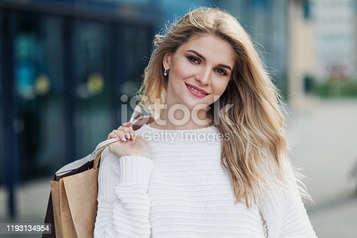Young attractive pregnant blonde woman in a white sweater against the backdrop of the city streets. Holding a lot of shopping bags. Sunny day.