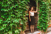 Young attractive romantic blonde hair curvy model posing against antique Roman Italian door. Dreaming, travel & vacation in old city center in Italy, Santarcangelo di Romagna. Picture with copy space