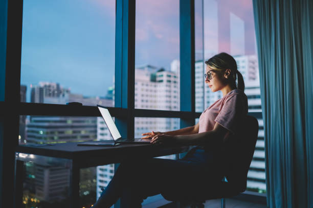 Young attractive skilled marketing expert in eyeglasses watching training webinar in webpage on laptop connected to 4G internet.Pretty hipster girl transferring money online via banking service stock photo