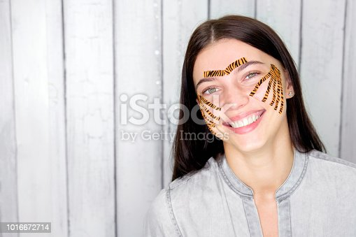 istock Young attractive smiling brunette woman with tiger colored tapes after taping face procedure in beauty parlor 1016672714