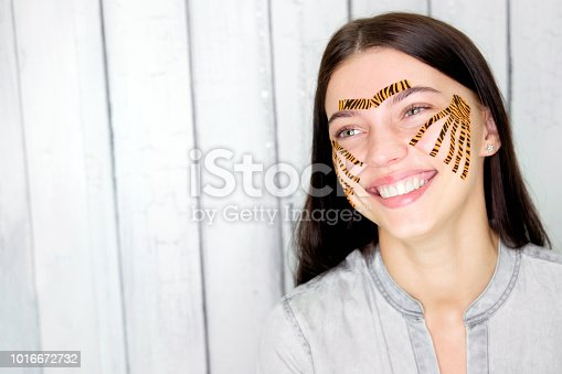 istock Young attractive smiling brunette woman with tiger colored tapes after taping face procedure in beauty parlor 1016672732