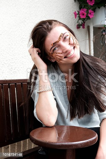 istock Young attractive smiling brunette woman with tiger colored tapes after taping face procedure in beauty parlor sitting in street 1016734148