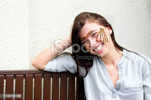istock Young attractive smiling brunette woman with tiger colored tapes after taping face procedure in beauty parlor sitting in street 1016734158