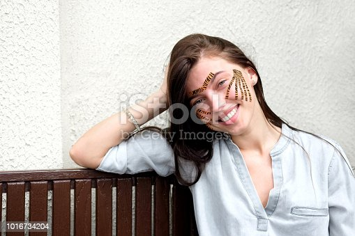 istock Young attractive smiling brunette woman with tiger colored tapes after taping face procedure in beauty parlor sitting in street 1016734204