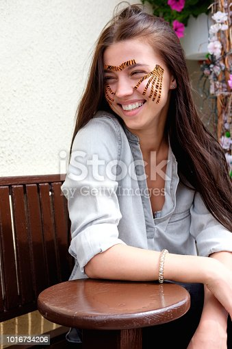 istock Young attractive smiling brunette woman with tiger colored tapes after taping face procedure in beauty parlor sitting in street 1016734206