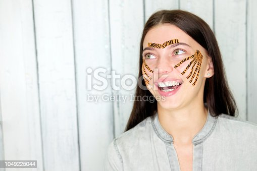 istock Young attractive smiling brunette woman with tiger colored tapes after taping face procedure in beauty parlor 1049225044