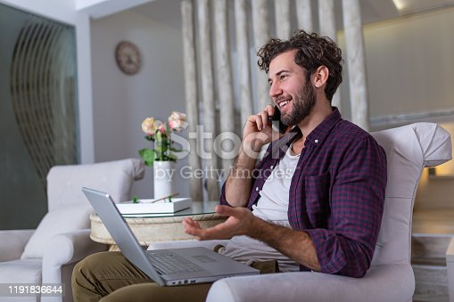 1127582480istockphoto Young attractive smiling guy is browsing at his laptop and talking oh mobile phone, sitting at home on the cozy sofa, wearing casual outfit. Freelance business work from home concept 1191836644