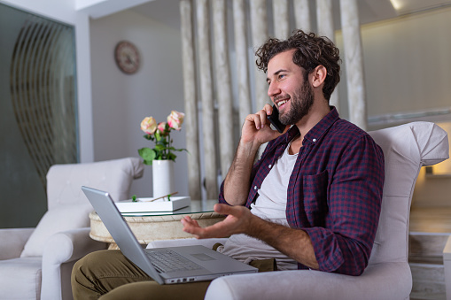 1127582480 istock photo Young attractive smiling guy is browsing at his laptop and talking oh mobile phone, sitting at home on the cozy sofa, wearing casual outfit. Freelance business work from home concept 1191836644