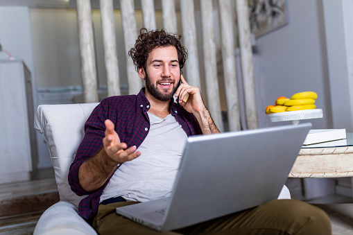 1127582480 istock photo Young attractive smiling guy is browsing at his laptop and talking oh mobile phone, sitting at home on the cozy sofa, wearing casual outfit. Freelance business work from home concept 1191836714