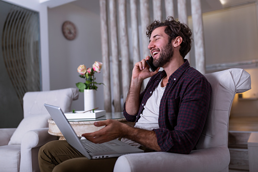 1127582480 istock photo Young attractive smiling guy is browsing at his laptop and talking oh mobile phone, sitting at home on the cozy sofa, wearing casual outfit. Freelance business work from home concept 1213169328