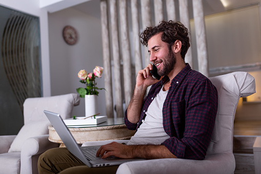 1127582480 istock photo Young attractive smiling guy is browsing at his laptop and talking oh mobile phone, sitting at home on the cozy sofa, wearing casual outfit. Freelance business work from home concept 1213169583