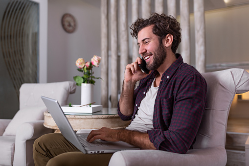 1127582480 istock photo Young attractive smiling guy is browsing at his laptop and talking oh mobile phone, sitting at home on the cozy sofa, wearing casual outfit. Freelance business work from home concept 1263539047