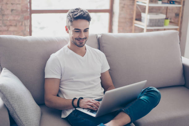 young attractive smiling guy is browsing at his laptop, sitting at home on the cozy beige sofa at home, wearing casual outfit - guy sofa foto e immagini stock