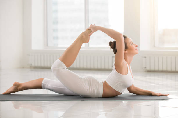 Young attractive smiling woman in Dhanurasana pose, white color stock photo