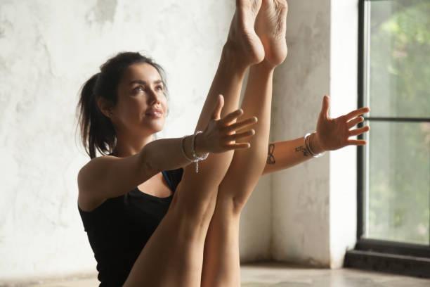 junge attraktive lächelnde frau in paripurna navasana darstellen, studio-hintergrund - gymnastik tattoo stock-fotos und bilder