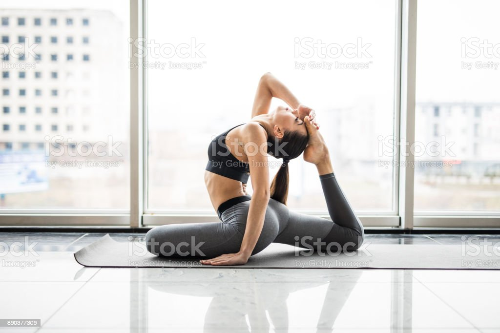 Young attractive smiling woman practicing yoga agaist panoramic window, sitting in One Legged King Pigeon exercise, Eka Pada Rajakapotasana pose, working out, wearing sportswear, grey pants, bra, indoor full length, home stock photo