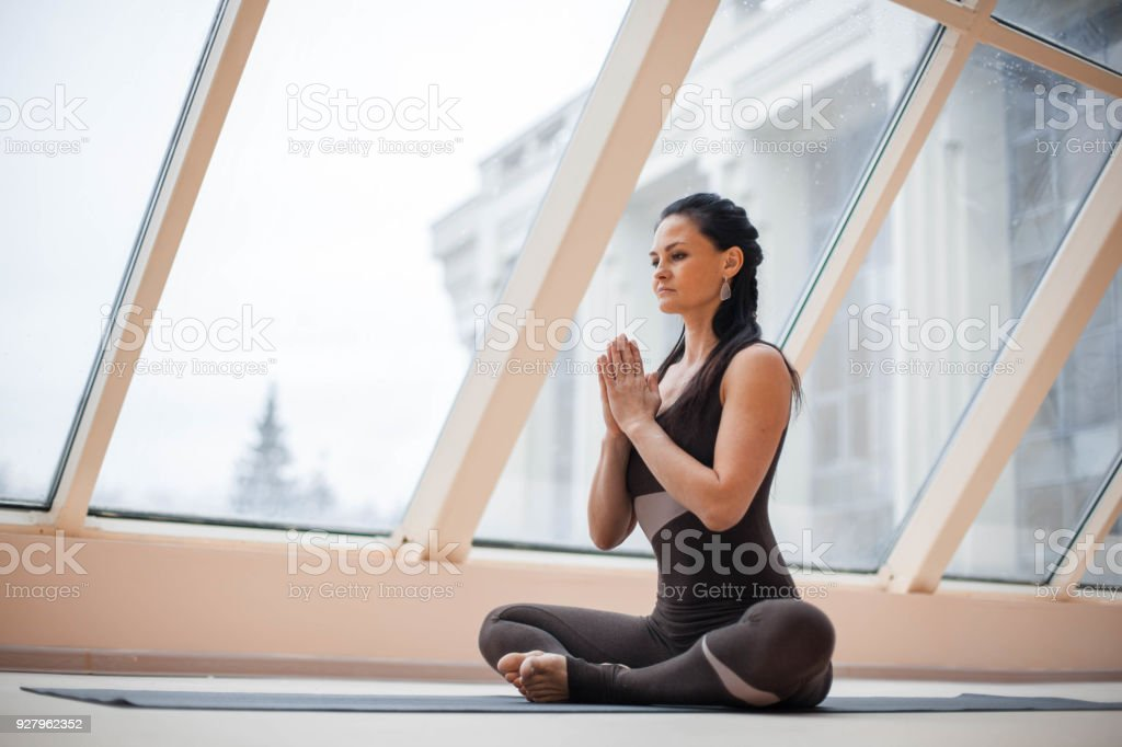 Young attractive smiling woman practicing yoga, sitting in Half Lotus exercise in fronte large windows, Ardha Padmasana pose, working out, wearing sportswear. stock photo