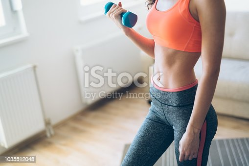 1035512048istockphoto Young attractive sportswoman doing exercises at home 1035512048