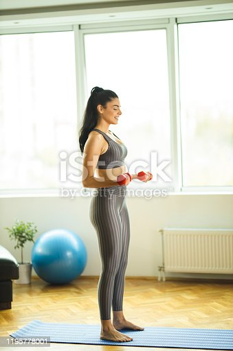 1035512048istockphoto Young attractive sportswoman doing exercises with weights at home 1195778001