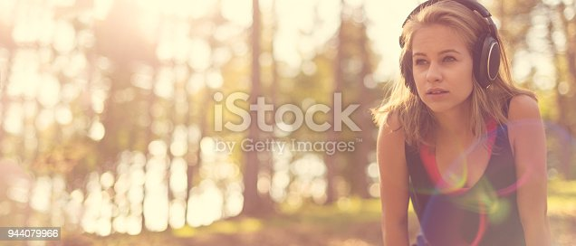Young attractive sportswoman listening to music wearing headphones. Sport, fitness, workout web banner.