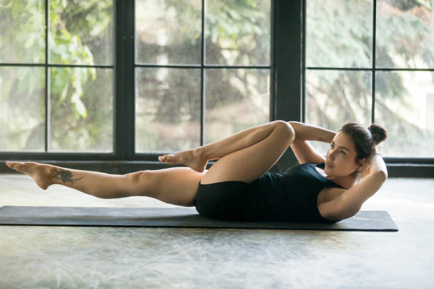 young attractive sporty woman doing bicycle crunches exercise - peso mosca foto e immagini stock