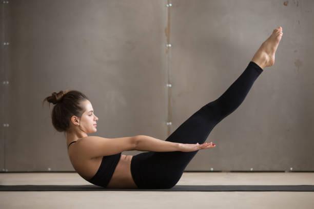 young attractive sporty woman doing boat pose, grey studio backg - peso mosca foto e immagini stock