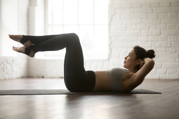 young attractive sporty woman practicing sit ups exercise, studi - peso mosca foto e immagini stock