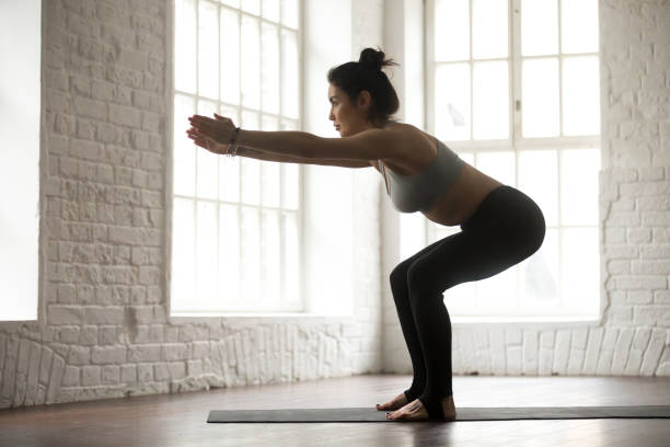 young attractive sporty woman practicing squats, white loft stud - peso mosca foto e immagini stock