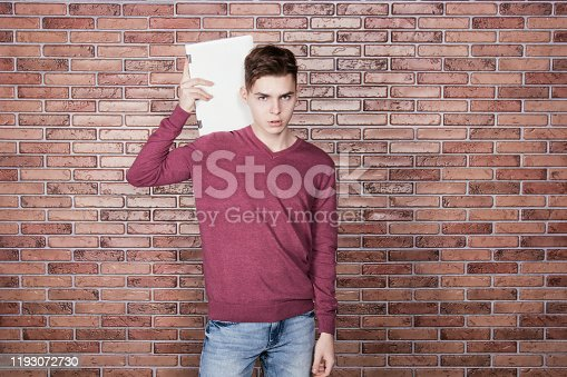 944992706 istock photo Young attractive student with a laptop 1193072730