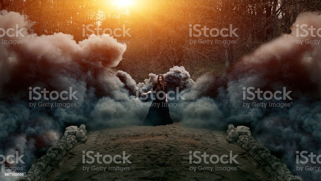 Young attractive Witch walking on the bridge in heavy black smoke. stock photo