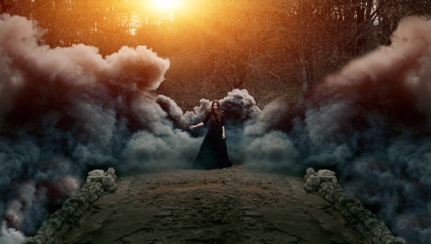 young attractive witch walking on the bridge in heavy black smoke. - fantasy stock photos and pictures