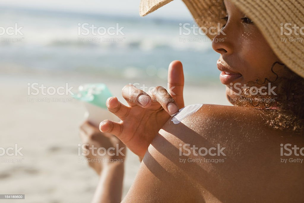 Young attractive woman attentively applying sunscreen on her sho stock photo