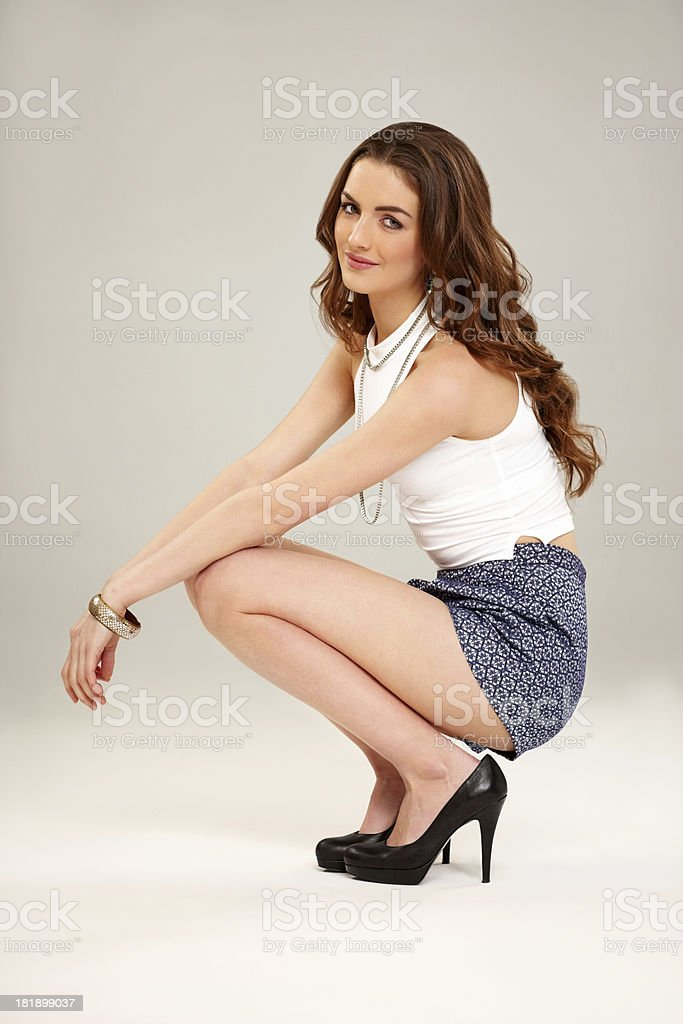 Young attractive woman crouching on grey background royalty-free stock photo