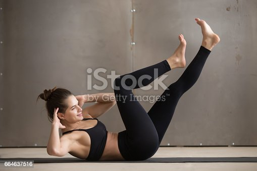 914755474 istock photo Young attractive woman doing bicycle crunches, grey studio backg 664637516