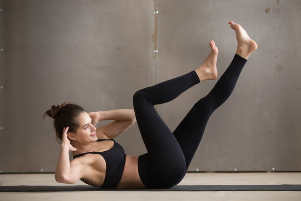young attractive woman doing bicycle crunches, grey studio backg - sit ups stock photos and pictures