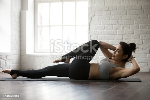 914755474 istock photo Young attractive woman doing bicycle crunches pose, white loft s 674564354
