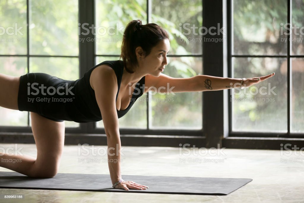 Young attractive woman doing Donkey Kick exercise, home background stock photo
