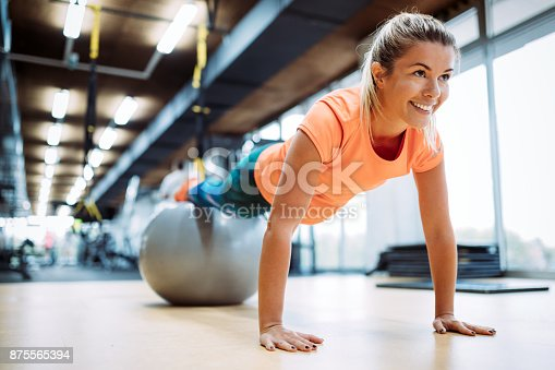 Young attractive woman doing push ups using ball in gym