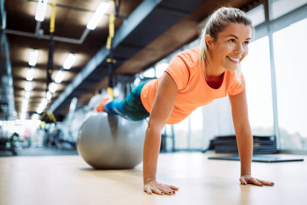 young attractive woman doing push ups using ball - push up stock photos and pictures