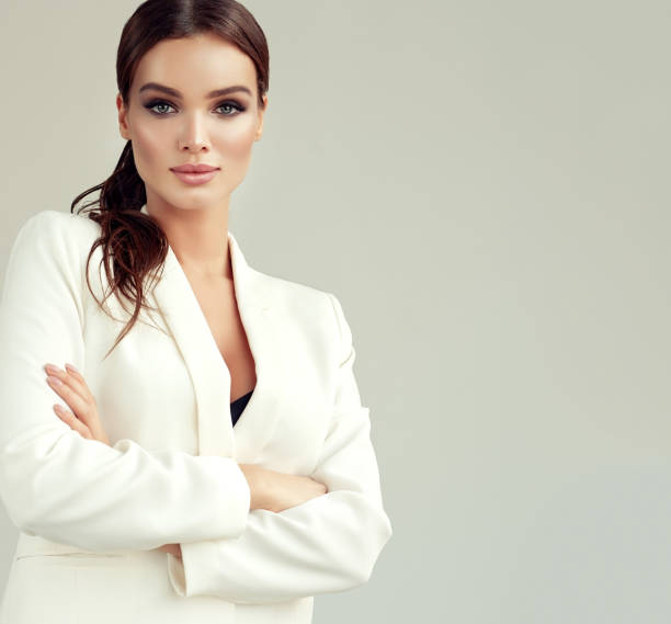 Young attractive woman dressed in a white suit jacket. Makeup and cosmetology. stock photo