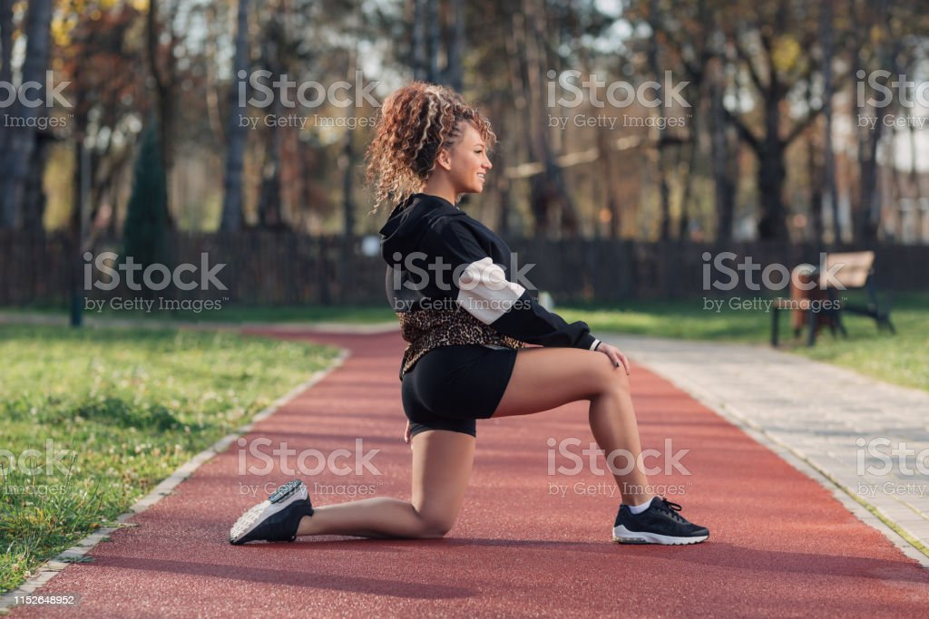Young attractive woman enjoying outdoor physical exercise in the park...
