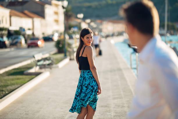 Jeune femme séduisante, flirter avec un homme dans la rue. Sexy femme souriante regardant en arrière sur un bel homme. Attraction femelle. L'amour à première vue. Réunion ex petit ami - Photo
