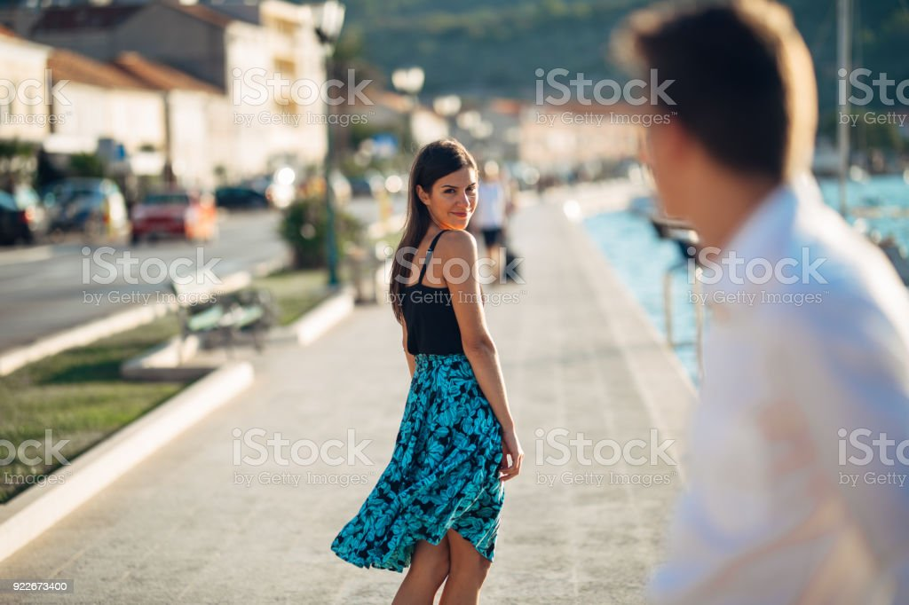 Young attractive woman flirting with a man on the street.Flirty smiling woman looking back on a handsome man.Female attraction.Love at first sight.Meeting ex boyfriend stock photo