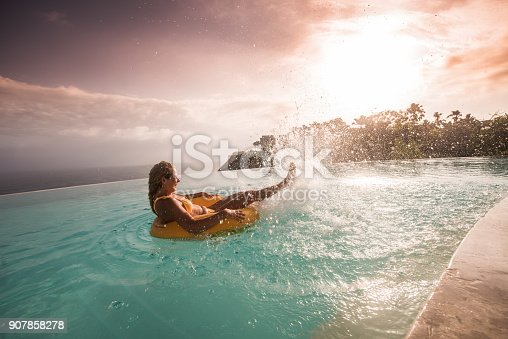 istock Young attractive woman having fun in float on infinity pool at sunset. 907858278