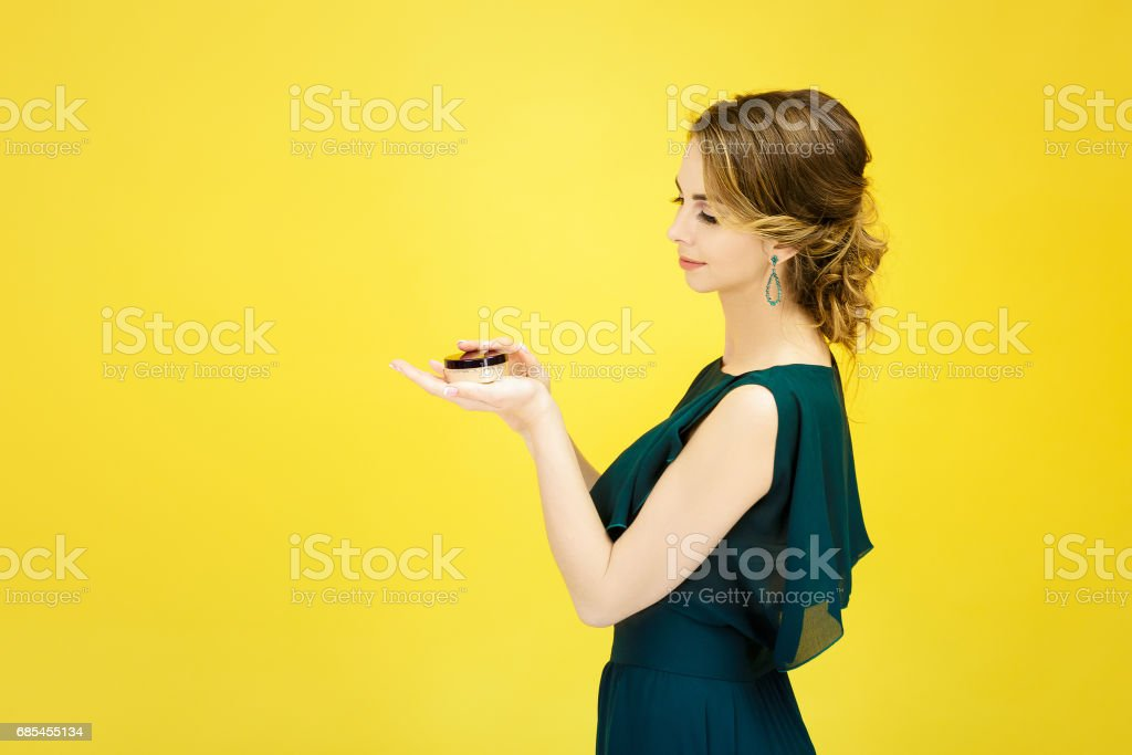 young attractive woman holding face powder on yellow background foto de stock royalty-free