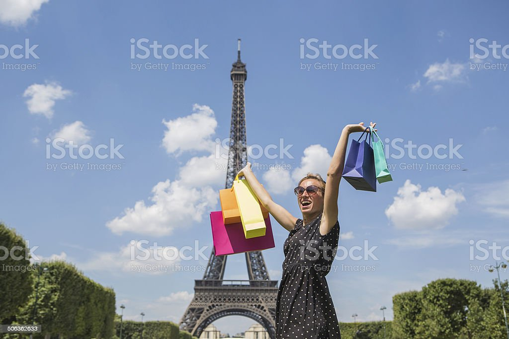 Young attractive woman holding shopping bags near Eiffel tower, PAris royalty-free stock photo