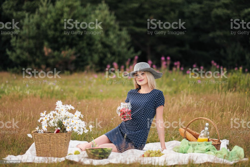 Young attractive woman in a blue dress at an outdoor picnic. A basket...